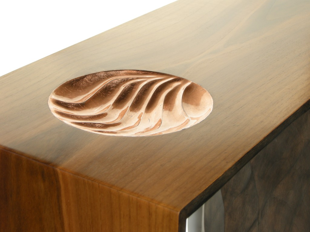 A console table made in walnut, with a carved and copper leaf bowl in the top and blackened carving on the underside